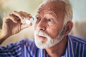 Man Putting Eye Drops Into His Eye